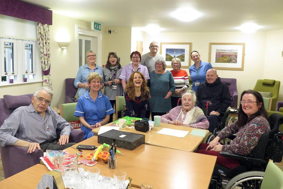 Anna Woodford with a group of workshop participants in a Hospice poetry workshop